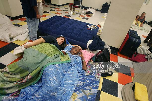 Karen Rosales and Marshall Tousant rest together at the Booker T Washington Senior High School Red Cross evacuation shelter as Tropical Storm Ernesto...