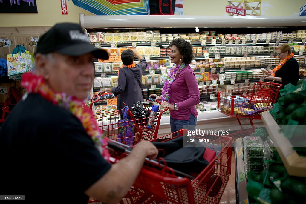 Karen Shane (C) and other shoppers enjoy the grand opening of a Trader Joe's on October 18, 2013 in Pinecrest, Florida. Trader Joe's opened its first store in South Florida where shoppers can now take advantage of the California grocery chains low-cost wines and unique items not found in other stores. About 80 percent of what they sell is under the Trader Joe's private label.