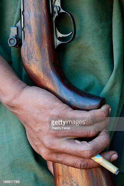 Karen villager hold a hunting gun and a cheroot the local cigar
