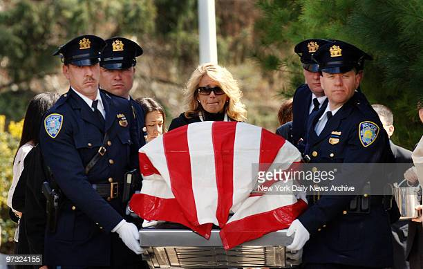 Karen Vitale cries as the coffin of her husband retired Port Authority officer Steven Vitale is carried from Our Lady Star of the Sea Church on...