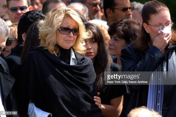 Karen Vitale with daughters Dawn Marie Stefanie and Michelle cries as the coffin of her husband retired Port Authority officer Steven Vitale is...