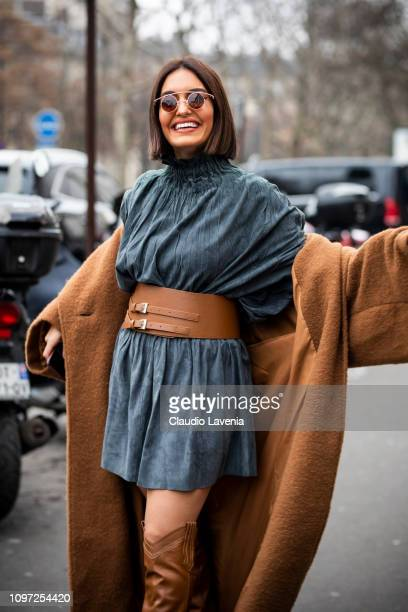 Karen Wazen Bakhazi wearing a blue dress tan leather belt long tan coat and tan leather boots is seen in the streets of Paris before the Acne Femme...