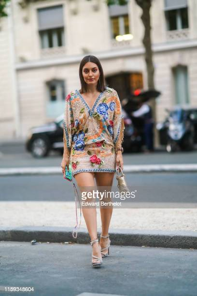 Karen Wazen Bakhazi wears earrings a colorful glittering embroidered and sequined vneck mini dress a shiny golden Lady Dior bag anklets glittering...