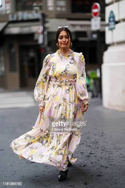Karen Wazen Bakhazi wears sunglasses, earrings, a colorful print gathered and ruffled long sleeves dress, shiny black crocodile pattern boots,...