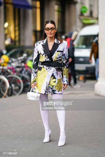 Karen Wazen wears sunglasses, necklaces, rings, a yellow, white and black floral print wrap-over mini dress with a black belt and black lapels, white...