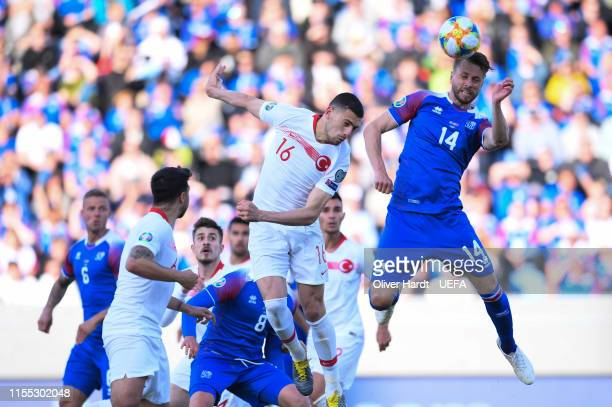 Kari Arnason of Iceland challenges for the ball with Merih Demiral of Turkey during the UEFA Euro 2020 Qualifier match between Iceland and Turkey at...