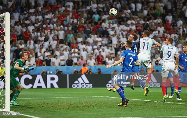 Kari Arnason of Iceland clears the ball in front of Jamie Vardy of England during the UEFA EURO 2016 round of 16 match between England and Iceland at...