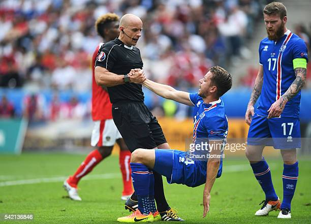 Kari Arnason of Iceland is helped up by the referee during the UEFA EURO 2016 Group F match between Iceland and Austria at Stade de France on June 22...
