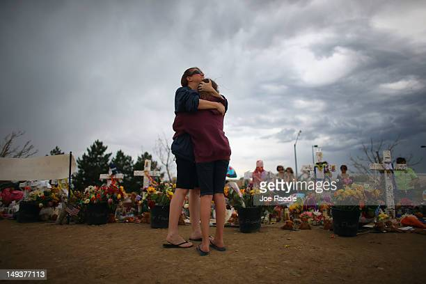 Kari Girard and her daughter Trinidy Girard hug at a memorial setup across the street from the Century 16 movie theatre on July 27 2012 in Aurora...