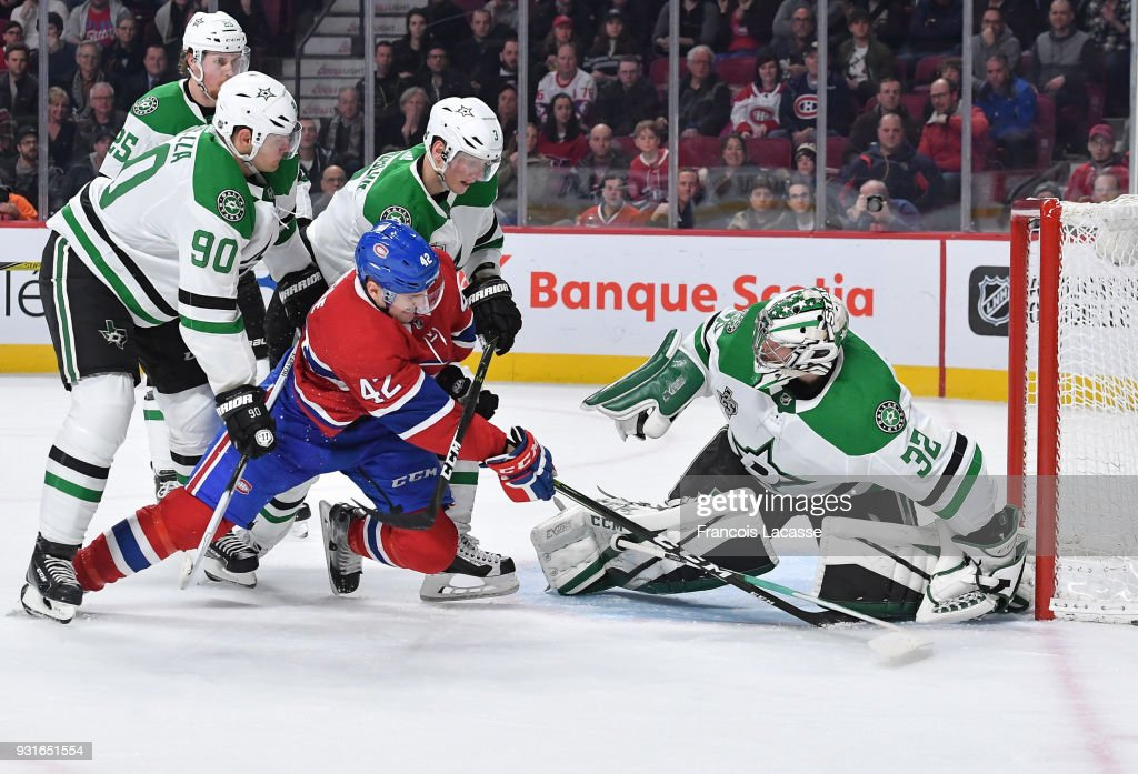 Kari Lehtonen #32 of the Dallas Stars covers up the puck with help from teammates, under pressure from Byron Froese #42 of the Montreal Canadiens in the NHL game at the Bell Centre on March 13, 2018 in Montreal, Quebec, Canada.