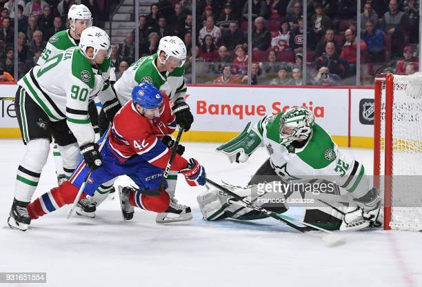 Kari Lehtonen of the Dallas Stars covers up the puck with help from teammates under pressure from Byron Froese of the Montreal Canadiens in the NHL...