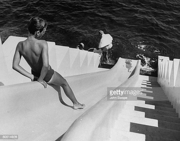 Karim AGA Khan IV on slide leading from Ali Khan's pool to the sea 25 feet below