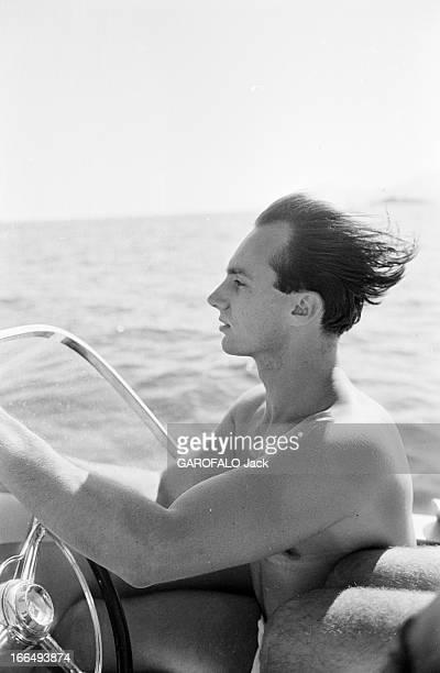 Karim Aga Khan On Holiday On The French Rivieira Aout 1959 sur la côte d' Azur portrait de KARIM AGA KHAN de profil cheveux au vent conduisant son...