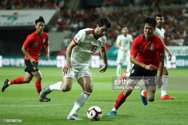 Karim Ansarifard of Iran competes for the ball with Kim Young-Gwon of South Korea during the international friendly match between South Korea and...