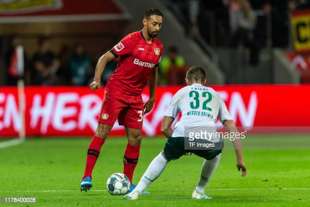 Karim Bellarabi of Bayer 04 Leverkusen and Marco Friedl of SV Werder Bremen battle for the ball during the Bundesliga match between Bayer 04...