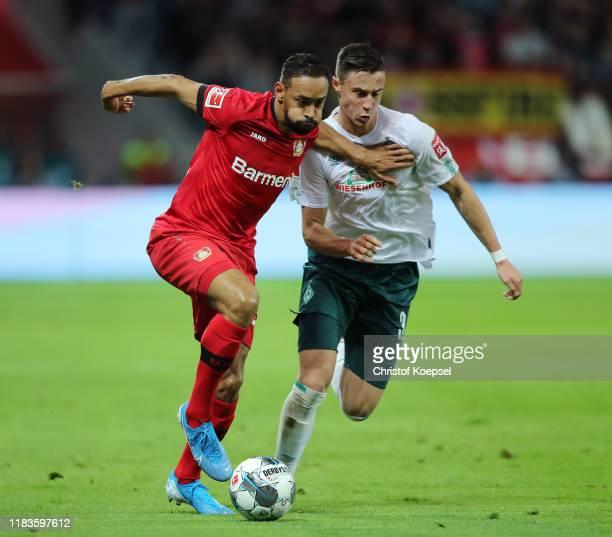Karim Bellarabi of Bayer 04 Leverkusen battles for possession with Marco Friedl of SV Werder Bremen during the Bundesliga match between Bayer 04...