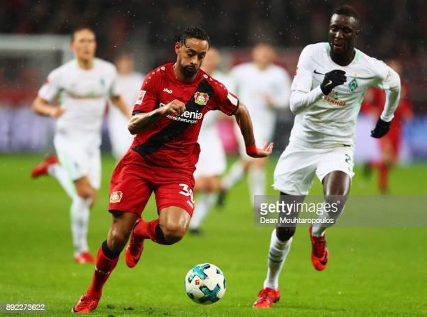 Karim Bellarabi of Bayer 04 Leverkusen gets past the tackle from Lamine Sane of Werder Bremen during the Bundesliga match between Bayer 04 Leverkusen...
