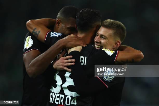 Karim Bellarabi of Bayer Leverkusen celebrates with his team mates Jonathan Tah and Mitchell Weiser after scoring his side's third goal during the...