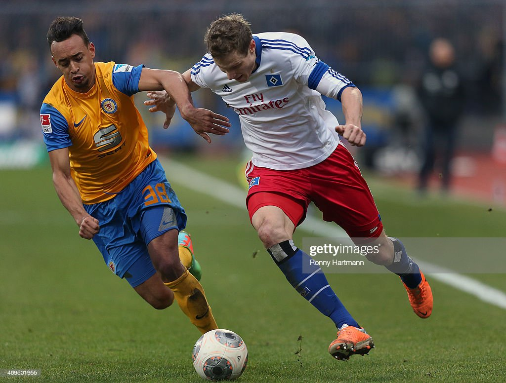 Karim Bellarabi (L) of Braunschweig and Marcell Jansen of Hamburg vie for the ball during the Bundesliga match between Eintracht Braunschweig and Hamburger SV at Eintracht Stadion on February 15, 2014 in Braunschweig, Germany.