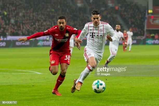 Karim Bellarabi of Leverkusen and James Rodriguez of Muenchen battle for the ball during the Bundesliga match between Bayer 04 Leverkusen and FC...
