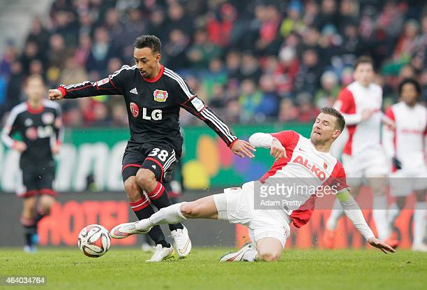 Karim Bellarbi of Bayer Leverkusen is challenged by Daniel Baier of FC Augsburg during the Bundesliga match between FC Augsburg and Bayer 04...