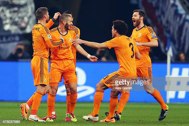 Karim Benzema 82L of Madrid celebrates his team's first goal with team mates during the UEFA Champions League Round of 16 first leg match between FC...