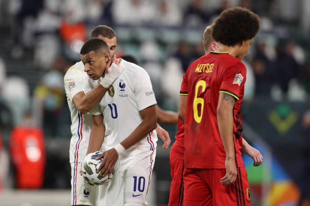Karim Benzema of France gives words of encouragement to team mate Kylian Mbappe before taking a penalty to level the scoreline at 2-2 during the UEFA...