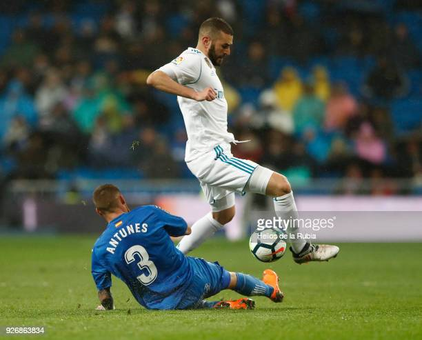 Karim Benzema of Real Madrid and Vitorino Antunes of Getafe compete for the ball during the La Liga match between Real Madrid and Getafe at Estadio...