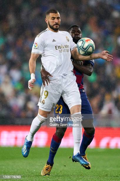 Karim Benzema of Real Madrid battles for the ball with Samuel Umtiti of FC Barcelona during the Liga match between Real Madrid CF and FC Barcelona at...