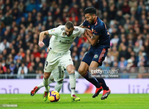 Karim Benzema of Real Madrid battles with Ezequiel Garay of Valencia during the La Liga match between Real Madrid CF and Valencia CF at Estadio...