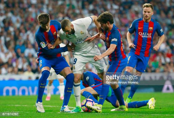 Karim Benzema of Real Madrid battles with Gerard Pique and Sergi Roberto of Barcelona during the La Liga match between Real Madrid CF and FC...