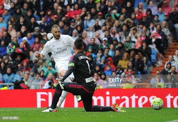 Karim Benzema of Real Madrid beats Diego Alves of Valencia CF to score his team's 2nd goal during the La Liga match between Real Madrid CF and...