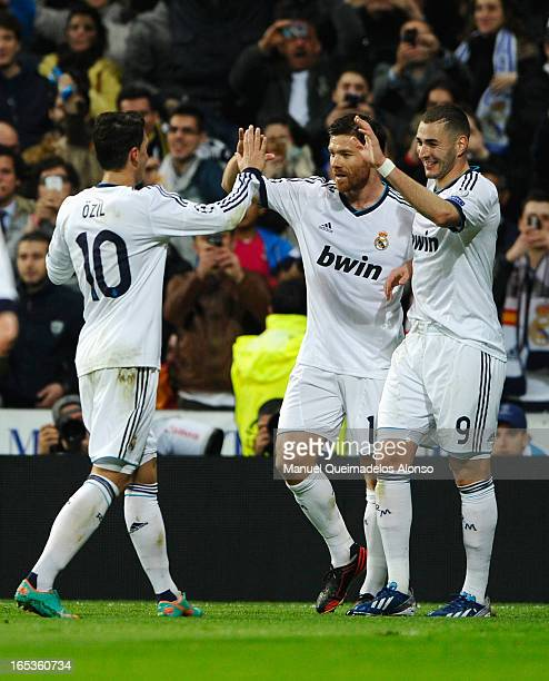 Karim Benzema of Real Madrid celebrates his goal with Xabi Alonso and Mesut Oezil during the UEFA Champions League Quarter Final first leg match...