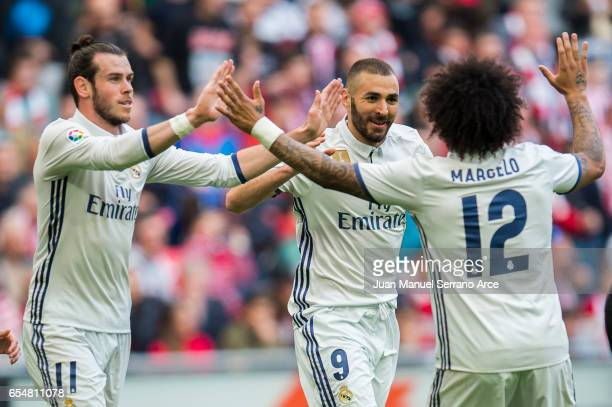 Karim Benzema of Real Madrid celebrates with his teammate Gareth Bale and Marcelo Vieira da Silva of Real Madrid after scoring the opening goal...