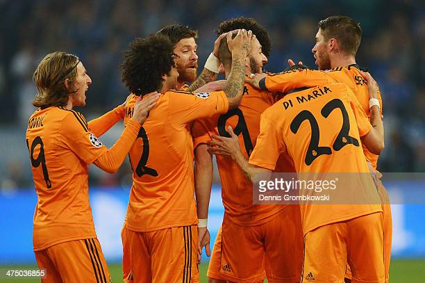 Karim Benzema of Real Madrid celebrates with team mates after scoring his team's first goal during the UEFA Champions League Round of 16 first leg...