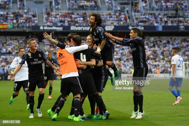 Karim Benzema of Real Madrid celebrates with team mates after scoring his sides second goal during the La Liga match between Malaga and Real Madrid...