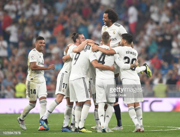 Karim Benzema of Real Madrid celebrates with teammates after scoring his teams second goal during the La Liga match between Real Madrid CF and CD...