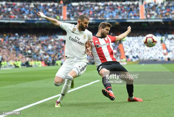 Karim Benzema of Real Madrid CF battles for the ball with Inigo Martinez of Athletic Club during the La Liga match between Real Madrid CF and...