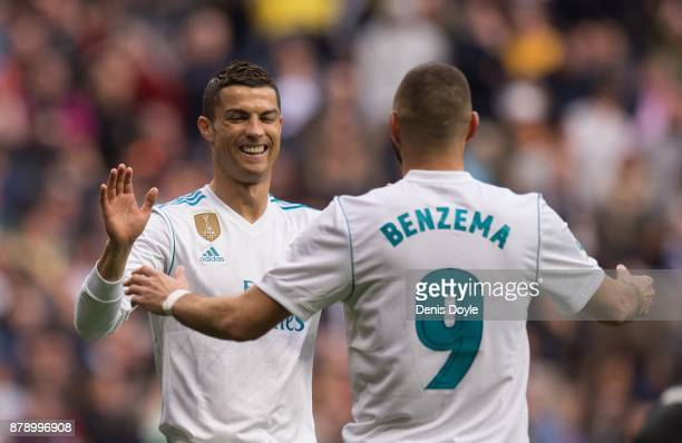 Karim Benzema of Real Madrid CF celebrates with Cristiano Ronaldo after scoring his team's opening goal during the La Liga match between Real Madrid...