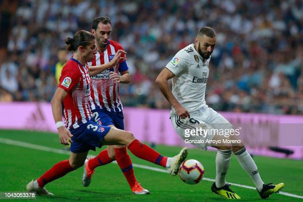 Karim Benzema of Real Madrid CF competes for the ball with Filipe Luis of Atletico de Madrid and his teammate Diego Godin during the La Liga match...