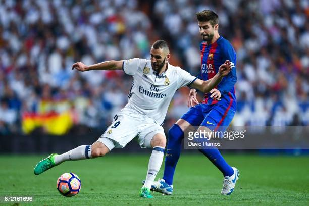 Karim Benzema of Real Madrid CF competes for the ball with Gerard Pique of FC Barcelona during the La Liga match between Real Madrid CF and FC...