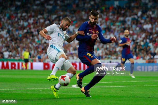 Karim Benzema of Real Madrid CF competes for the ball with Gerard Pique of FC Barcelona during the Supercopa de Espana Final 2nd Leg match between...