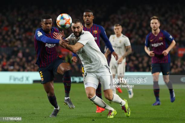 Karim Benzema of Real Madrid CF competes for the ball with Nelso Semedo of FC Barcelona during the Copa del Semi Final first leg match between...