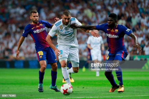 Karim Benzema of Real Madrid CF competes for the ball with Samuel Umiti of FC Barcelona and his teammate Jordi Alba during the Supercopa de Espana...