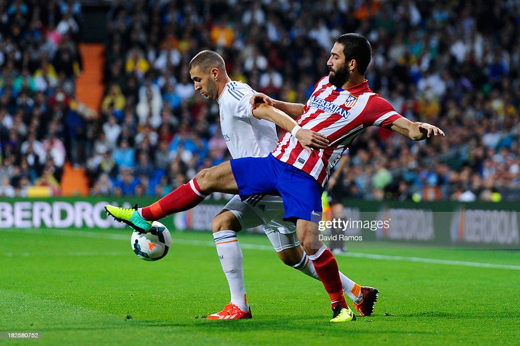 Karim Benzema of Real Madrid CF duels for the ball with Arda Turan of Atletico de Madrid during the La Liga match between Real Madrid CF and Club Atletico de Madrid at Bernabeu on September 28, 2013 in Madrid, Spain.
