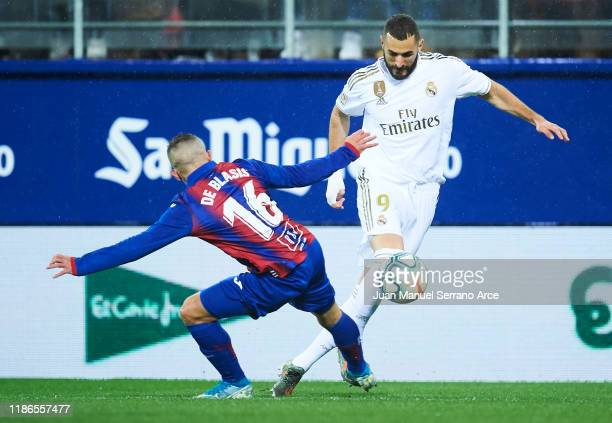 Karim Benzema of Real Madrid CF duels for the ball with Pablo De Blasis of SD Eibar during the Liga match between SD Eibar SAD and Real Madrid CF at...