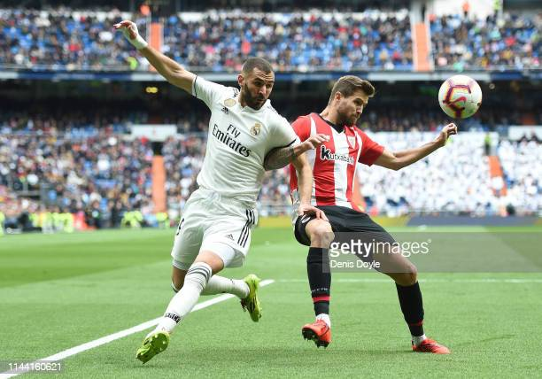 Karim Benzema of Real Madrid CF fouls Inigo Martinez of Athletic Club during the La Liga match between Real Madrid CF and Athletic Club at Estadio...