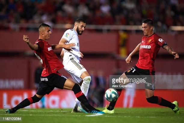 Karim Benzema of Real Madrid CF plays the ball between Martin Valjent and Antonio Jose Raillo of RCD Mallorca during the La Liga match between RCD...