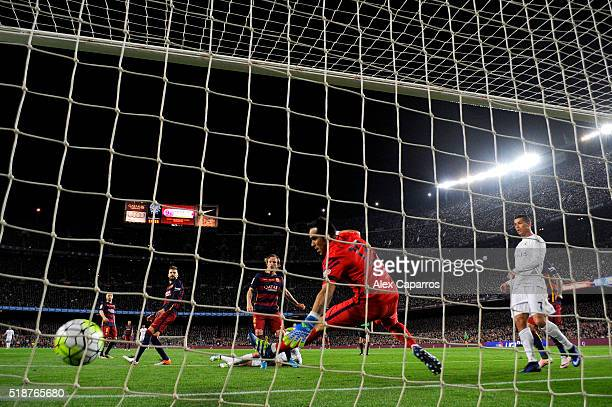Karim Benzema of Real Madrid CF scores his team's first goal past Claudio Bravo of FC Barcelona during the La Liga match between FC Barcelona and...