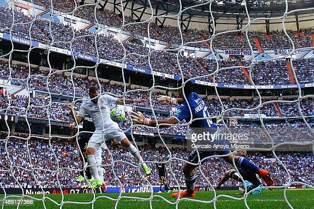 Karim Benzema of Real Madrid CF scores their opening goal against goalkeeper Andres Fernandez of Granada CF during the La Liga match between Real...